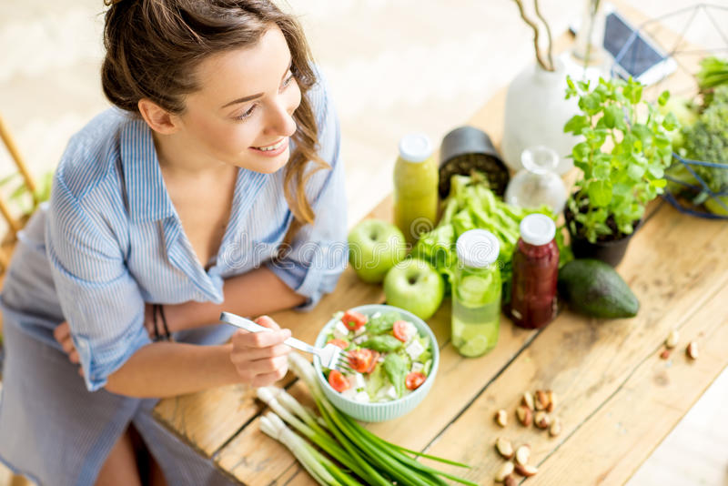 Woman eating healthy salad. Young and happy woman eating healthy salad sitting on the table with green fresh ingredients indoors stock photo