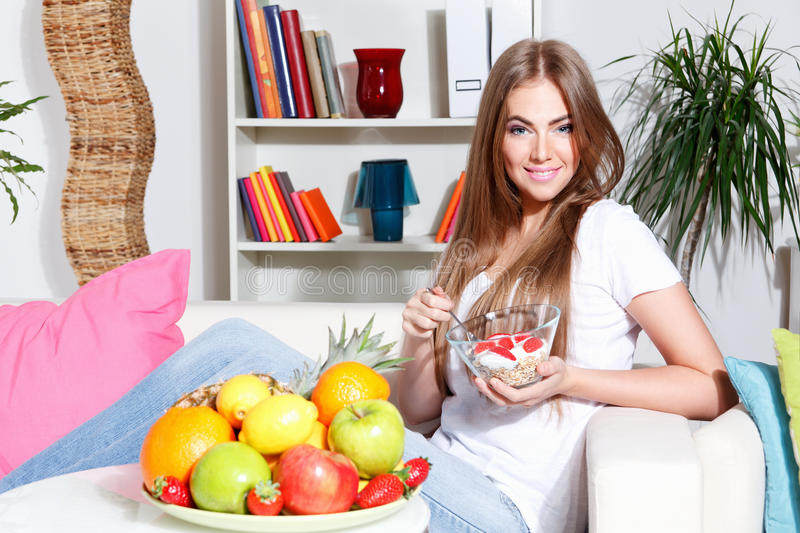 Woman eating healthy snack. Woman eating healthy breakfast on the couch stock photo