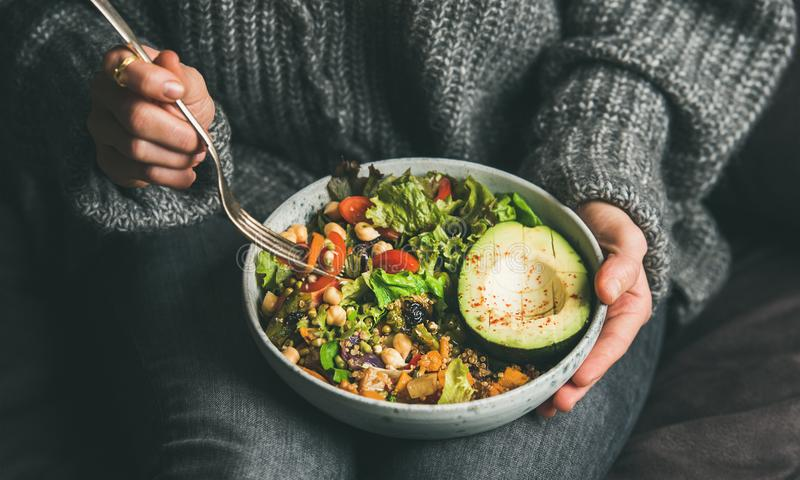 Woman eating healthy vegetarian dinner from Buddha bowl, close-up stock images