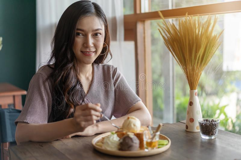 Woman eating honey toast, sweet dessert in cafe stock photo