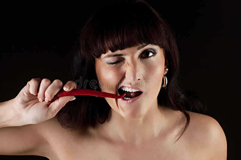 Woman eating hot spicy chili pepper royalty free stock photo