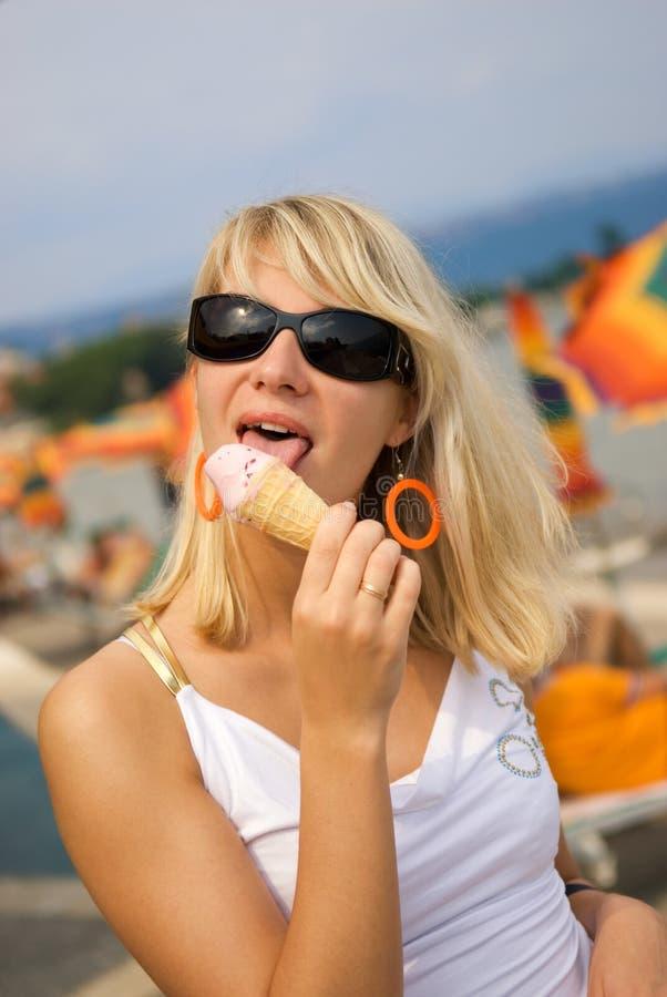 Woman eating ice-cream stock photos