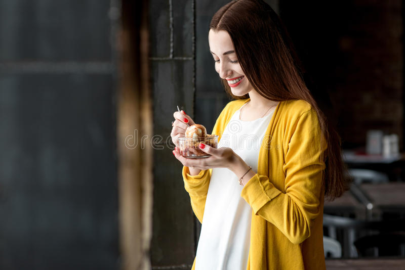 Woman eating ice cream in the cafe. Young smiling woman dressed in yellow sweater eating ice cream in the dark cafe interior royalty free stock photos