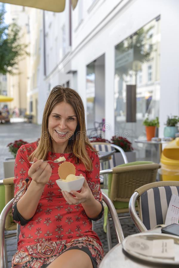 Woman eating ice cream outside on summer vacation stock images
