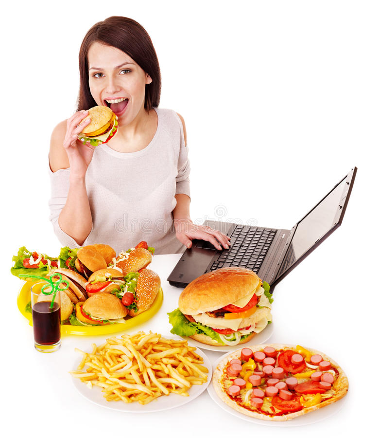 Woman eating junk food. Woman eating fast food at work. Isolated royalty free stock photos