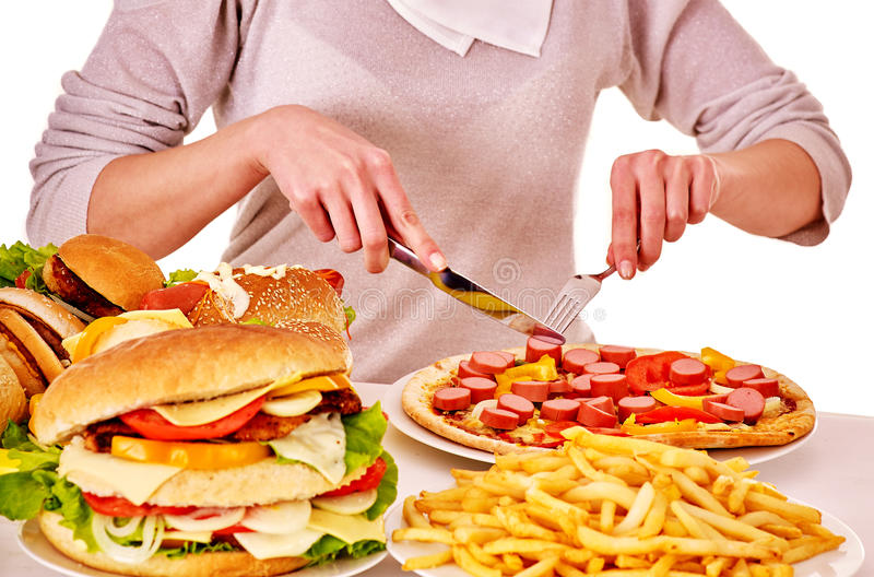 Woman eating junk food. Body part of woman eating pizza at table. Isolated royalty free stock photography
