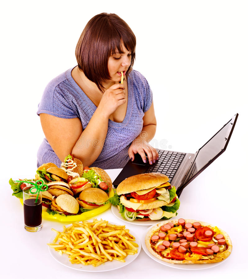 Woman eating junk food. Woman eating fast food at work. Isolated stock photo