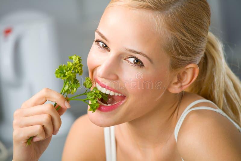 Woman eating at kitchen royalty free stock image
