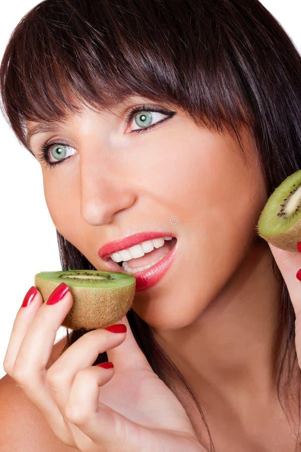 Woman eating kiwi royalty free stock photography