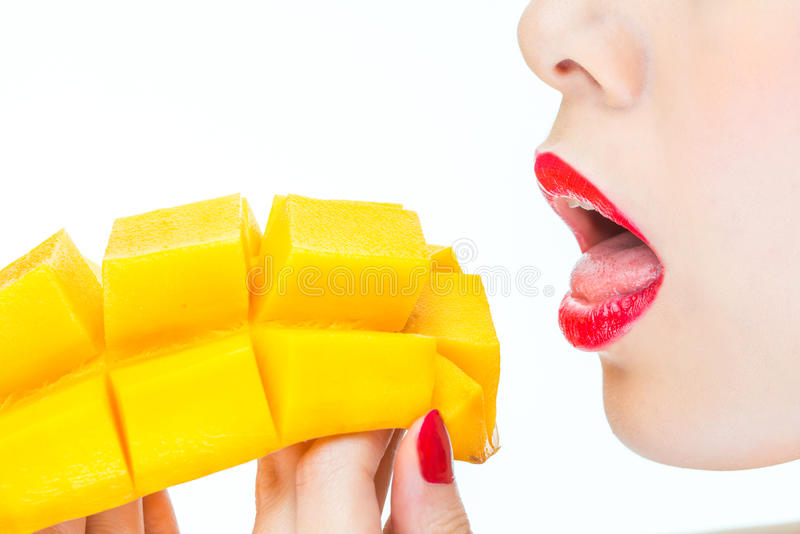Woman eating mango, sexy, healthy, lipstick, desire, bite royalty free stock images