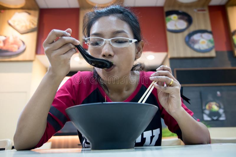 Woman eating a meal in an Asian restaurant stock photo