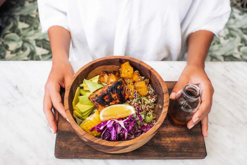 Fresh meal with fried salmon steak, quinoa avocado. Woman eating meal with fried salmon fish steak, quinoa, avocado, corn, cabbage salad and baked pumpkin in stock photography