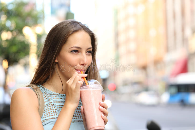 Woman eating a milkshake in the street. Pensive happy woman sipping a milkshake in the street stock photos