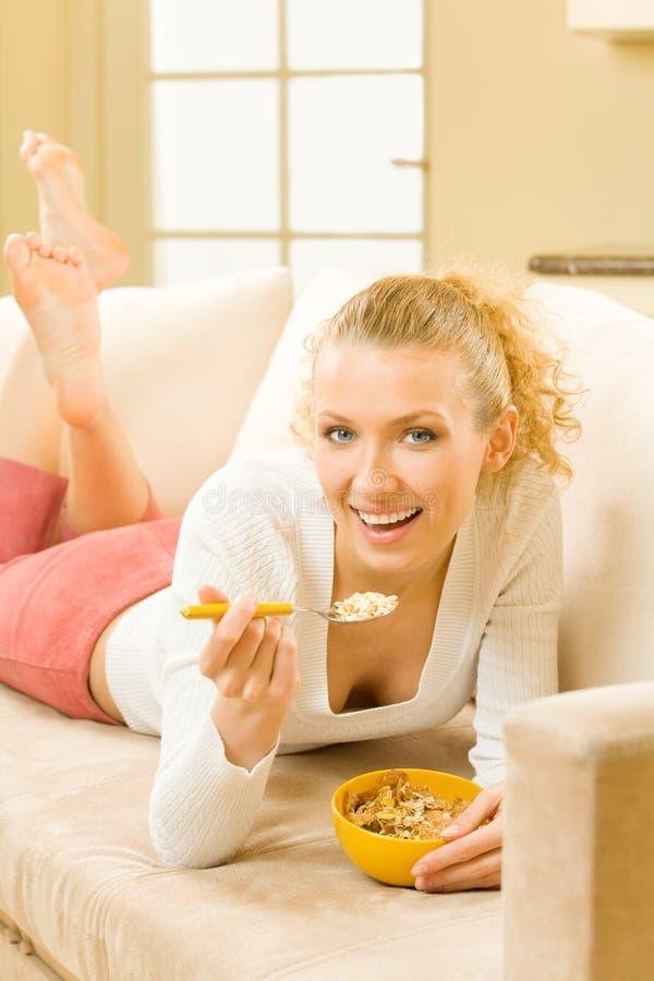 Woman eating muslin. At home stock photo