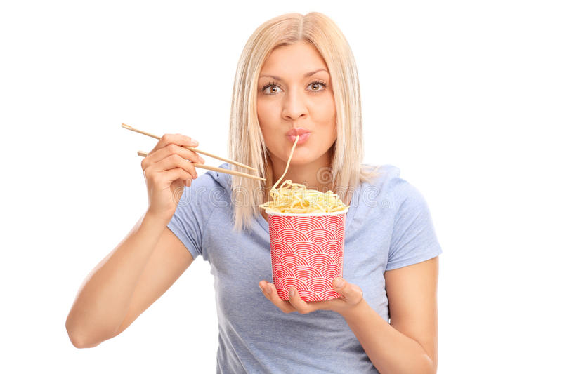 Woman eating noodles with Chinese sticks stock images