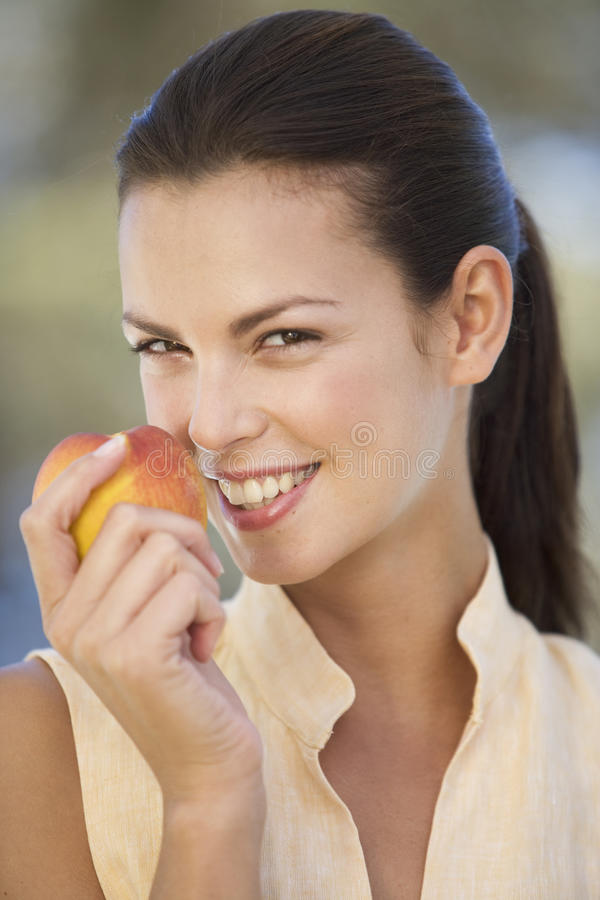 A woman eating a peach royalty free stock photography