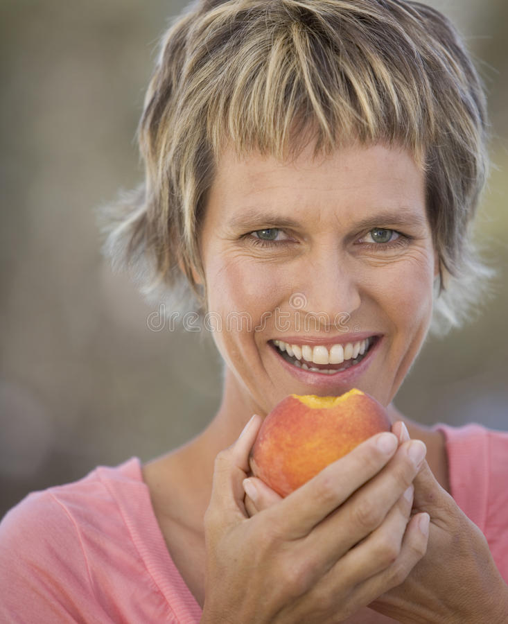 A woman eating a peach stock photography