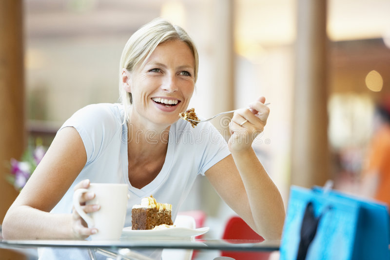 Woman Eating A Piece Of Cake At The Mall royalty free stock photos