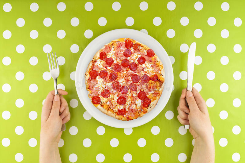 Woman Eating Pizza. Caucasian Female hands at dinner table holding fork and a knife above plate with served pepperoni pizza stock photos