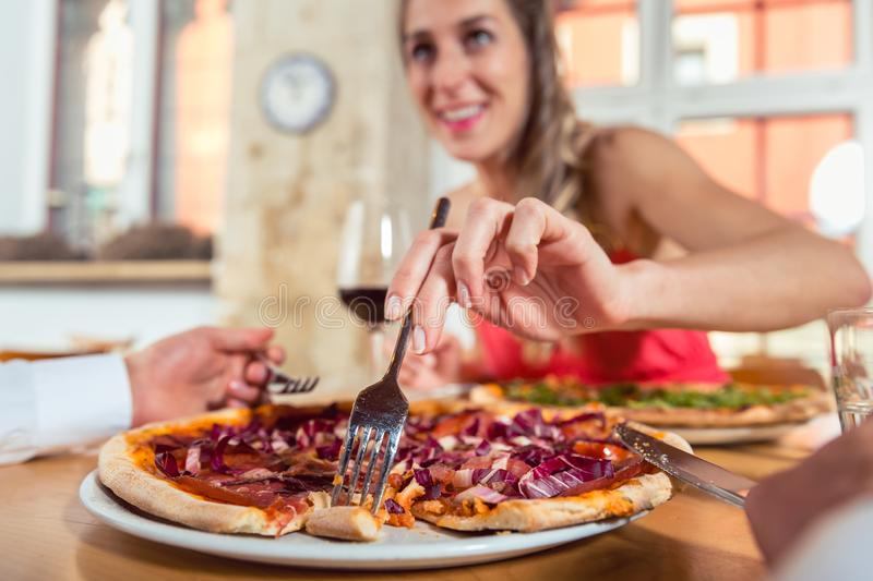 Woman eating pizza from her boyfriend`s plate royalty free stock photos