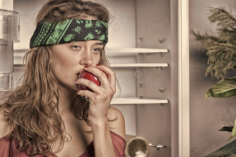 Woman eating red apple at open fridge stock photos