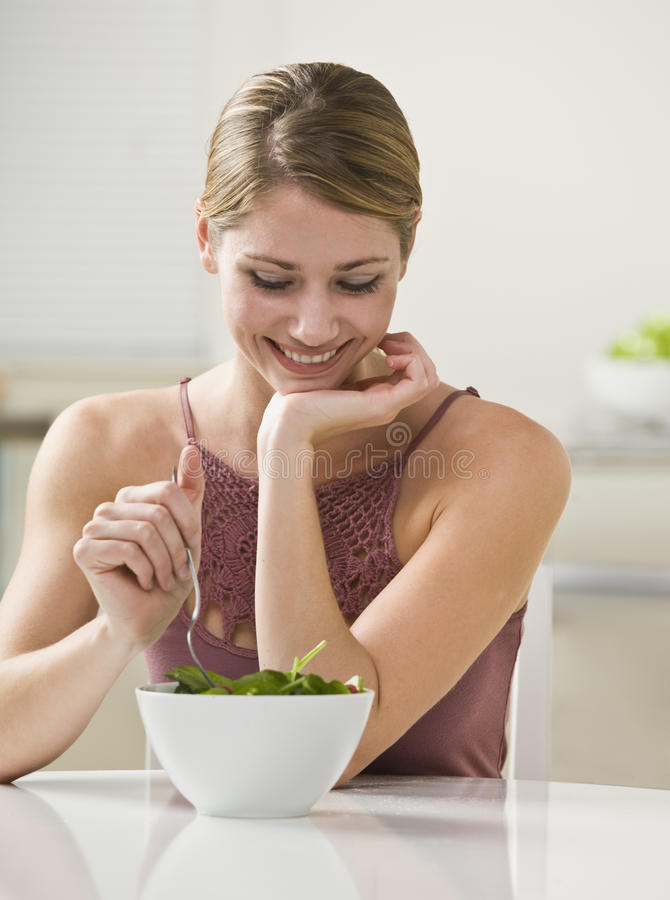 Woman Eating Salad. A young woman is eating salad and smiling. Vertically framed shot stock photo