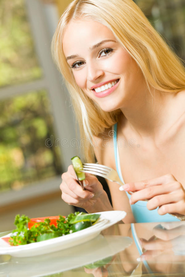 Woman eating salad. At home stock photography