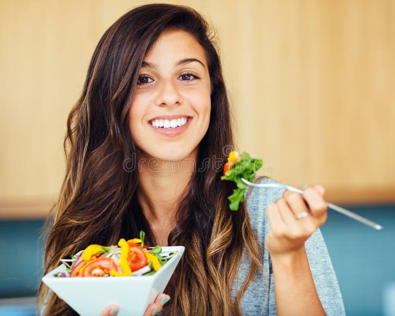 Woman eating salad. Attractive young woman eating salad royalty free stock photos