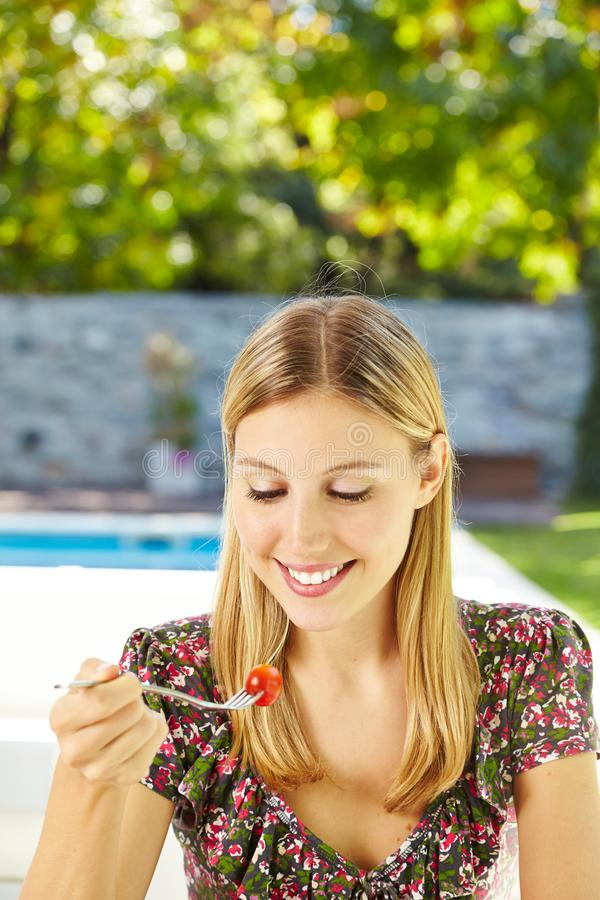 Woman is eating salad with fork royalty free stock image