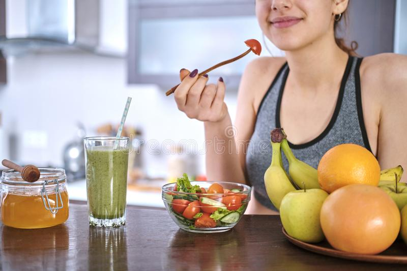 Woman eating salad on the home kitchen after a workout. royalty free stock photos