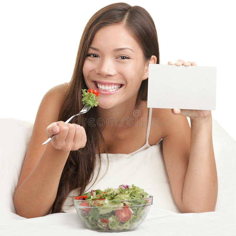 Woman Eating Salad showing copy space sign. Salad copyspace. Woman eating salad showing blank sign with copy space. Healthy eating concept with young asian woman stock photo