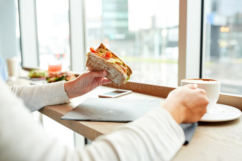 Woman eating sandwich and drinking coffee at cafe stock photos