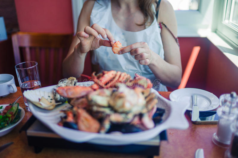 Woman eating seafood platter. A young woman is having a large seafood platter for lunch royalty free stock images