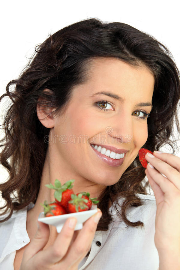Woman eating strawberries. Brunette woman eating strawberries with a spoon stock photo