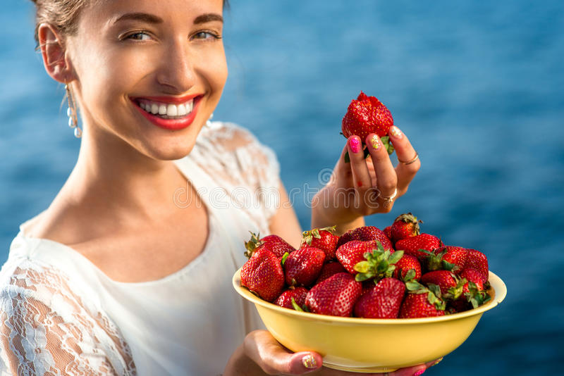 Woman eating strawberry stock image