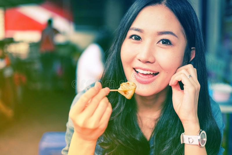 Woman eating Chinese steamed dumpling. Woman eating street food Chinese steamed dumpling stock photography