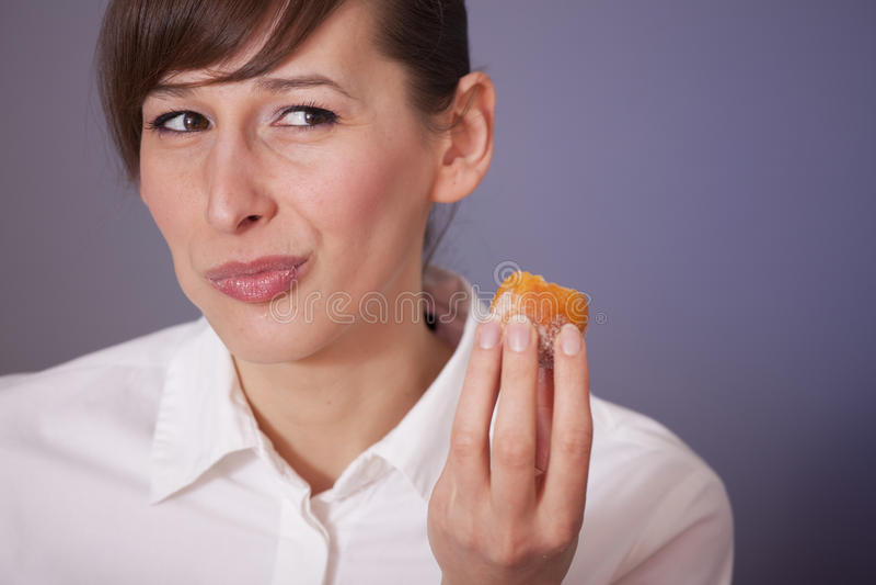 Woman eating sugar cake. Happy woman eating sugar cake over grey background royalty free stock image
