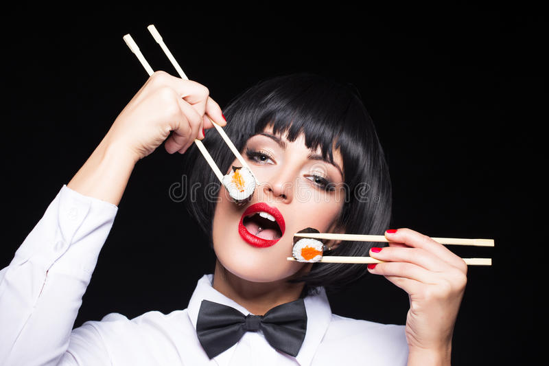 Woman eating sushi by two chopsticks. On black background stock photos