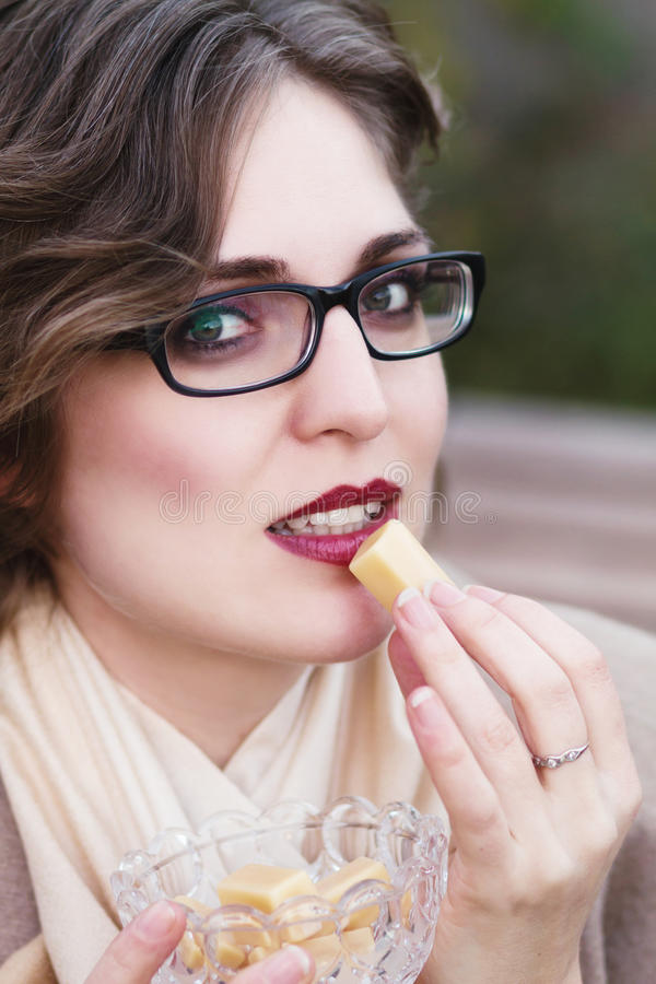 Woman eating sweet candy, toffee caramel. Young woman eating sweet candy, toffee caramel royalty free stock images