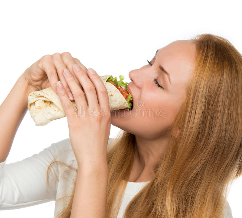 Woman eating tasty unhealthy twister sandwich in hands hungry. Woman eating tasty unhealthy burger twisted sandwich in hands hungry getting ready to eat isolated stock photo