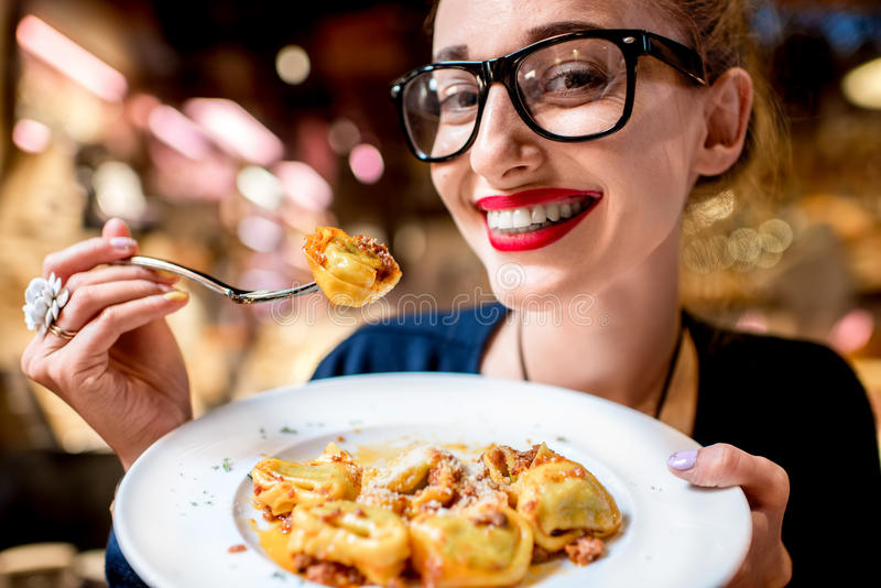 Woman eating tortellini pasta. Young woman eating tortellini pasta in front of the food shop in Bologna. Tortellini ring-shaped pasta was invented in Bologna stock photo