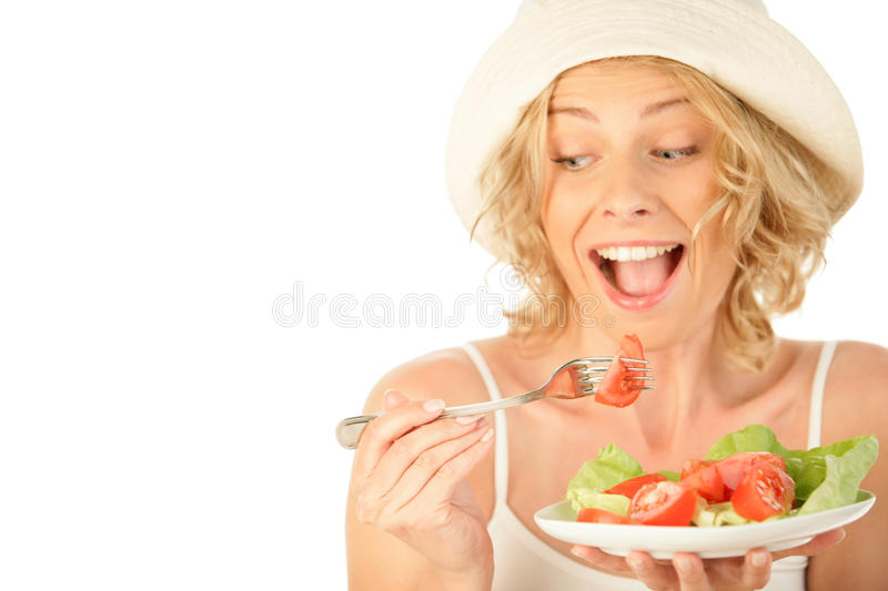 Woman eating vegetable salad. Blonde woman eating vegetable salad isolated on white background royalty free stock photography
