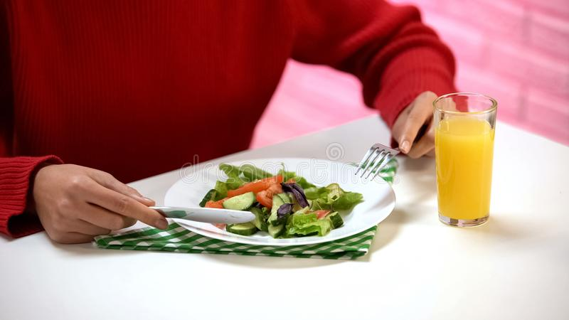 Woman eating vegetable salad with fork and knife, fresh orange juice on table stock photos