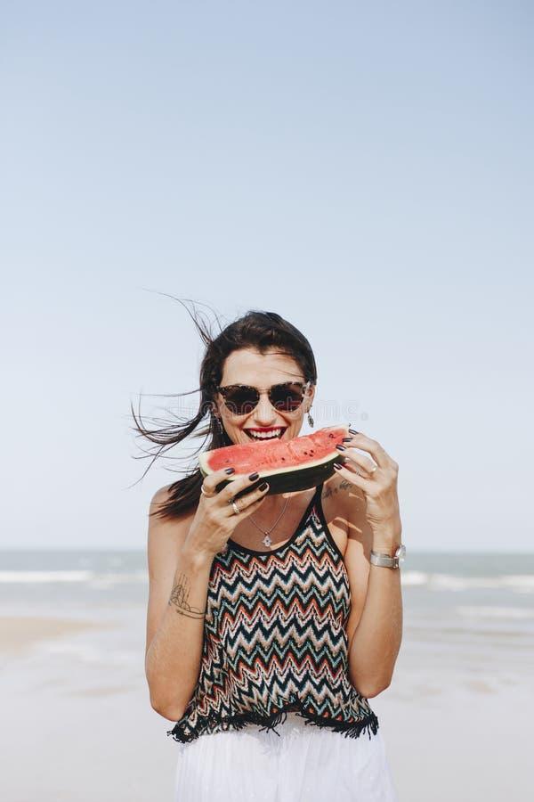 Woman eating watermelon at the beach stock photos