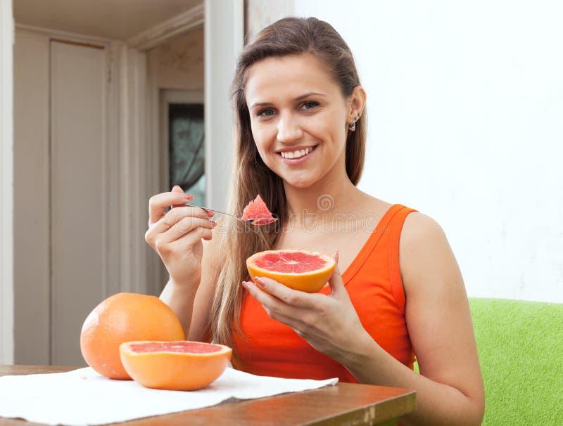 Woman eats grapefruit with spoon royalty free stock photos