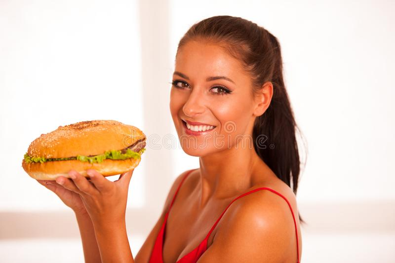Woman eats hamburger isolated over white background.  royalty free stock images