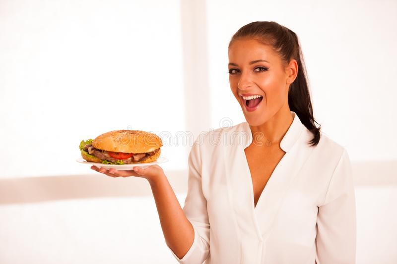 Woman eats hamburger isolated over white background.  stock photos