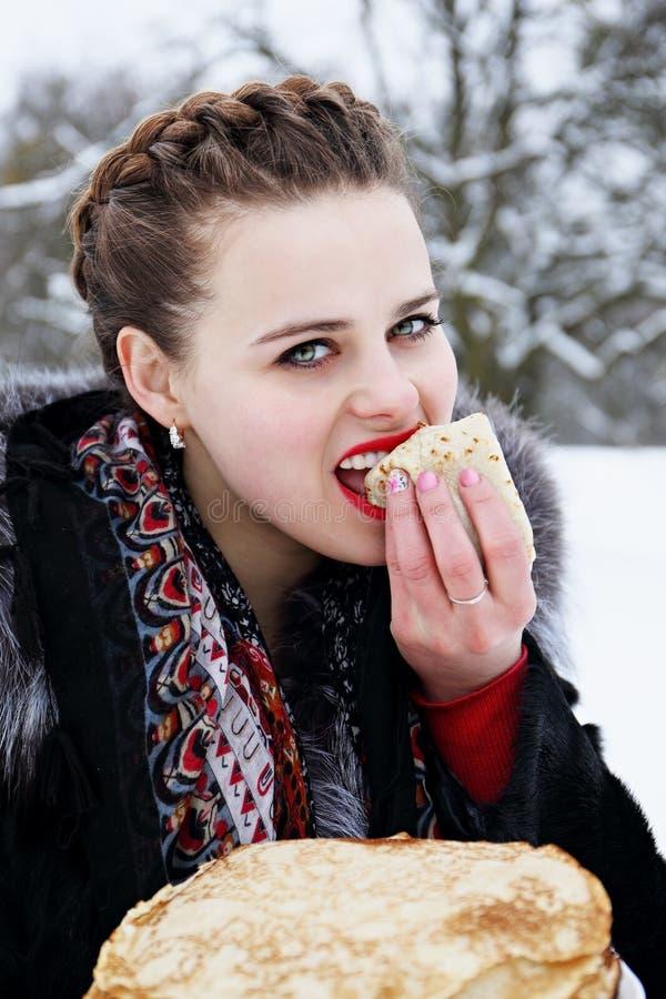 Woman eats a pancake royalty free stock image