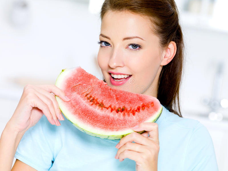 Woman eats a red water-melon stock photography