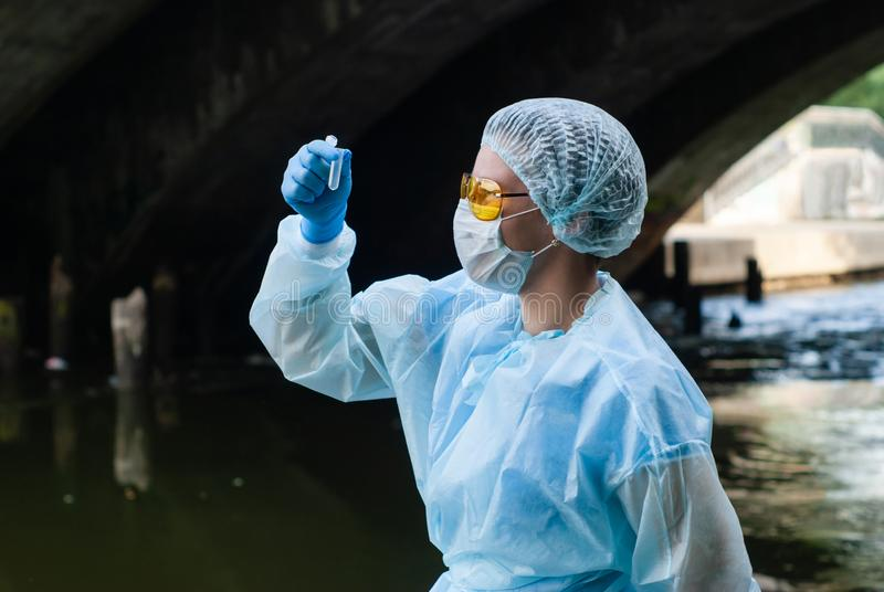 Woman ecologist or epidemiologist takes water analysis in city river. Female ecologist or epidemiologist takes test-tube water analysis in a city river under an stock photography